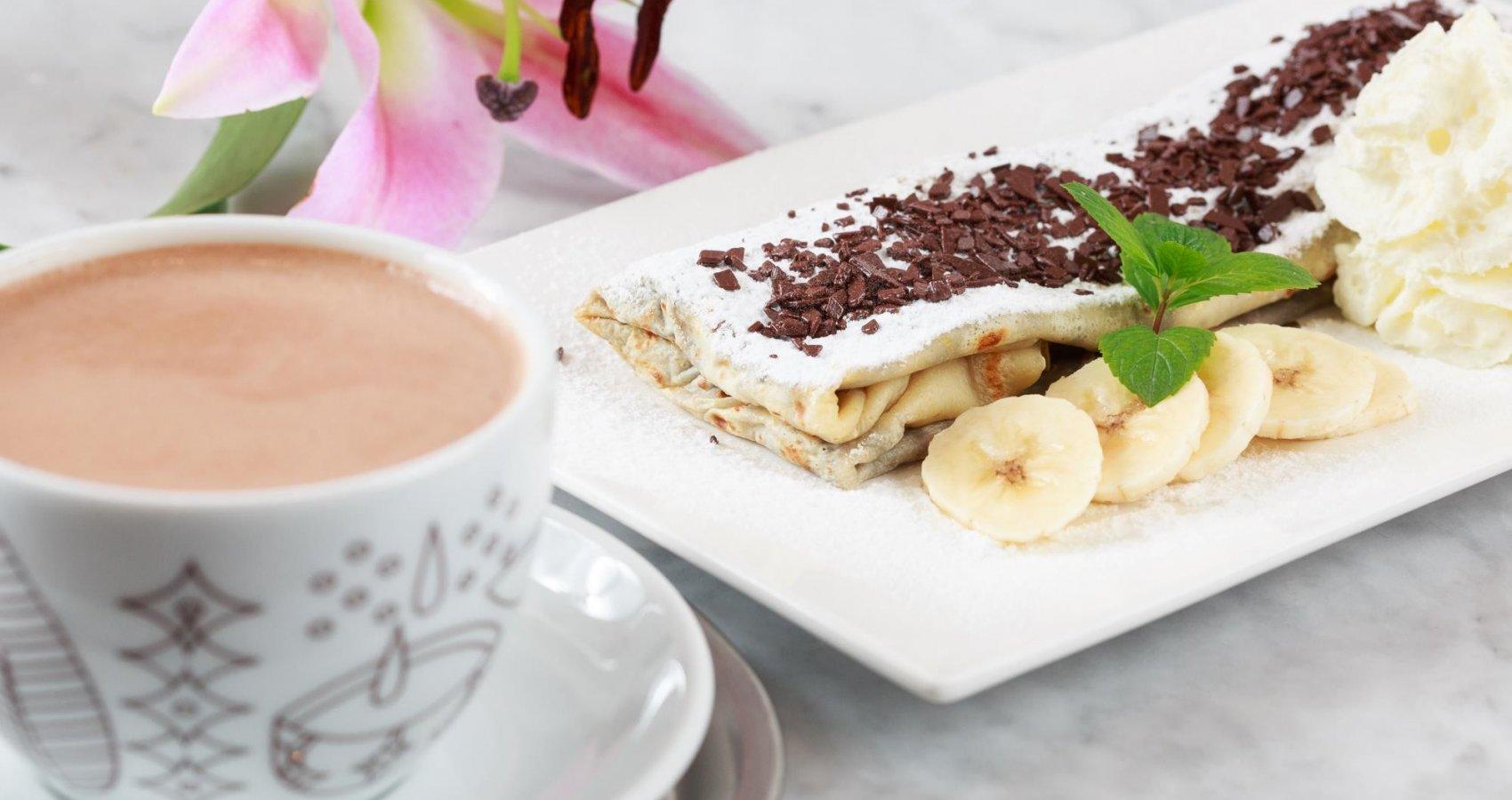 Palačinka s banánem a čokoládou a šálek horké čokolády